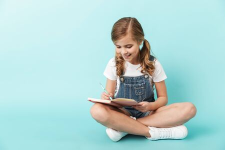 Portrait of a cheerful little girl isolated over blue background, writing in a notebook