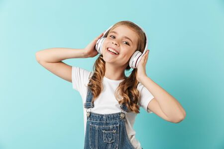 Portrait of a cheerful little girl isolated over blue background, wearing headphones 版權商用圖片