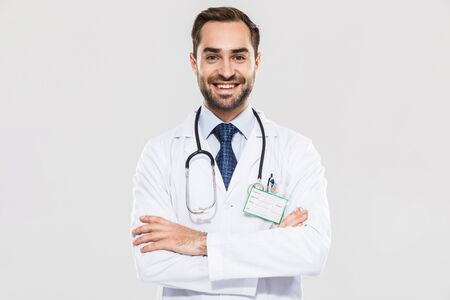 Portrait of brunette young medical doctor with stethoscope smiling at camera and standing wth arms crossed isolated over white background Zdjęcie Seryjne
