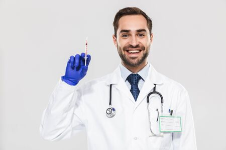 Portrait of caucasian young medical doctor wearing disposable sterile gloves working in hospital and holding syringe isolated over white background