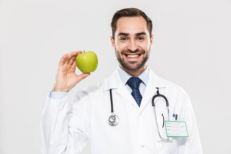 Portrait of happy young medical doctor working in hospital and holding green apple isolated over white background