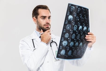Portrait of concentrated young medical doctor working in hospital and holding X-ray scan isolated over white background Zdjęcie Seryjne
