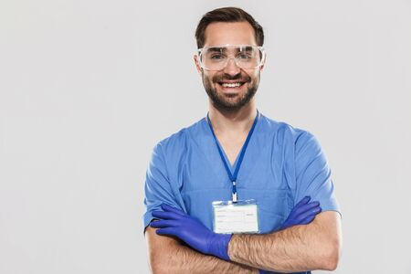 Portrait of cheerful young medical specialist working in hospital and wearing disposable sterile gloves isolated over white background Zdjęcie Seryjne