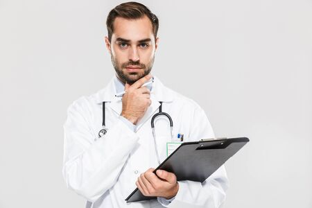 Portrait of professional young medical doctor looking at camera and holding health card isolated over white background