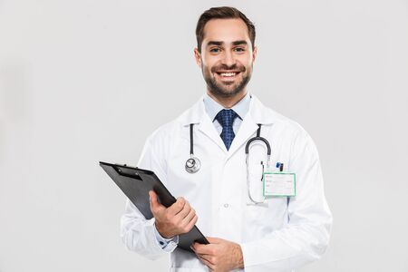 Portrait of european young medical doctor smiling at camera and holding health card isolated over white background