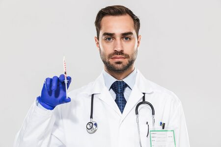 Portrait of european young medical doctor wearing disposable sterile gloves working in hospital and holding syringe isolated over white background