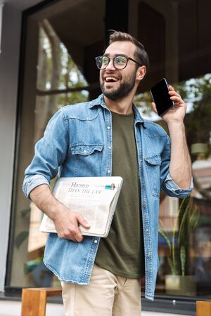 Photo of unshaved young man wearing earpods talking on smartphone while walking through city street with newspaper and laptop in hand Zdjęcie Seryjne