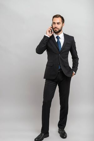 Full length of an attractive young businessman wearing suit standing isolated over gray background, talking on mobile phone