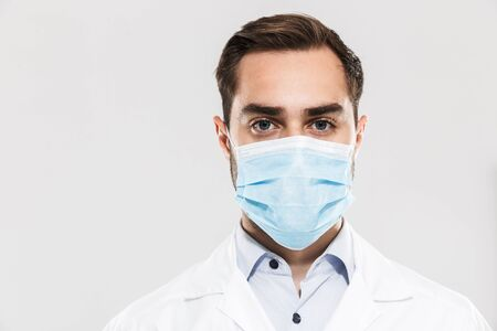 Portrait of european young medical doctor wearing sterile mask working in clinic laboratory and looking at camera isolated over white background
