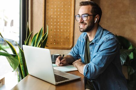 Photo of smiling bearded man wearing eyeglasses writing notes and using laptop while working in cafe indoors