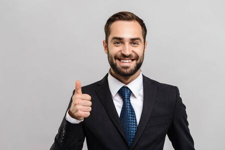 Attractive young businessman wearing suit standing isolated over gray background, thumbs up Zdjęcie Seryjne