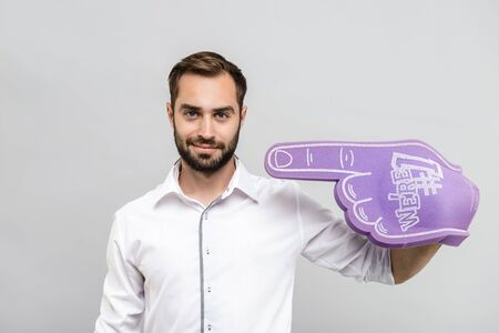 Portrait of a handsome young businessman wearing white shirt and tie standing isolated over gray background, wearing fan foam glove