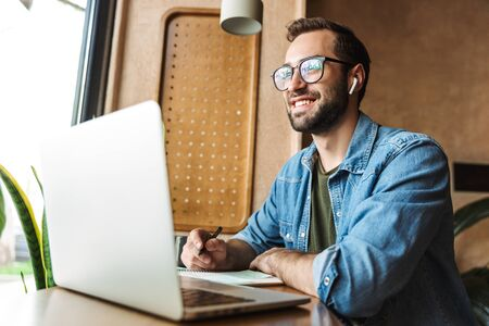 Photo of caucasian bearded man wearing eyeglasses writing notes and using laptop while working in cafe indoors