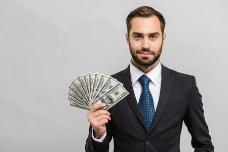 Attractive young businessman wearing suit standing isolated over gray background, showing money banknotes
