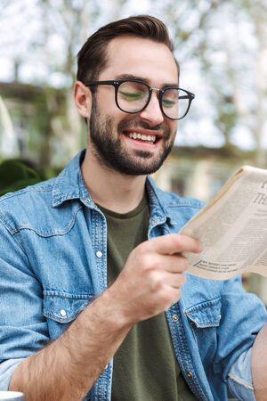 Photo of happy young man wearing eyeglasses smiling and reading newspaper while sitting in city cafe outdoors