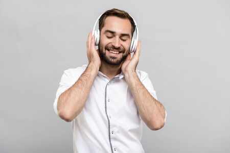 Portrait of a handsome young businessman wearing white shirt and tie standing isolated over gray background, listening to music with wireless headphones Zdjęcie Seryjne