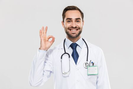 Portrait of handsome young medical doctor with stethoscope smiling at camera and showing ok sign isolated over white background
