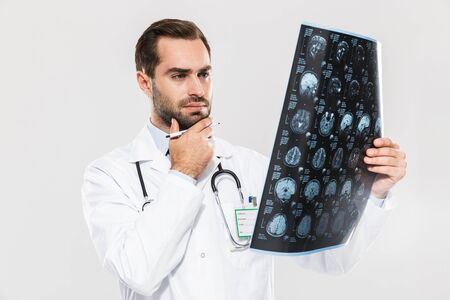 Portrait of smart young medical doctor working in hospital and holding X-ray scan isolated over white background