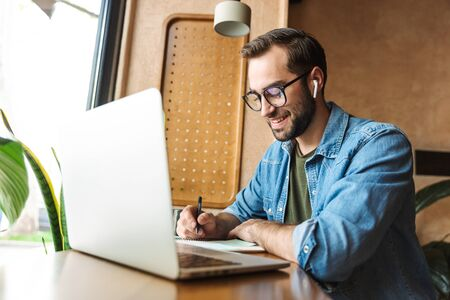 Photo of handsome bearded man wearing eyeglasses writing notes and using laptop while working in cafe indoors Zdjęcie Seryjne