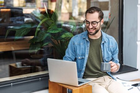Photo of bearded young man wearing eyeglasses holding cup of coffee and typing on laptop while working in city cafe outdoors