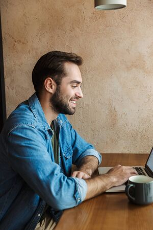 Image of handsome positive man wearing denim shirt smiling and using laptop while sitting at desk in cafe indoors
