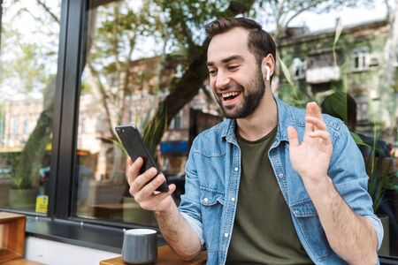 Photo of satisfied young man wearing earpods holding and talking on smartphone while sitting in city cafe outdoors