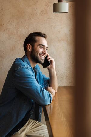 Photo of masculine satisfied man wearing denim shirt smiling and talking on cellphone while sitting on chair in cafe indoors