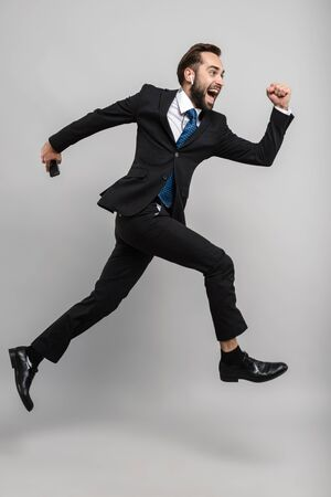 Full length of an attractive smiling young businessman wearing suit jumping isolated over gray background, wearing earphones, holding mobile phone Zdjęcie Seryjne