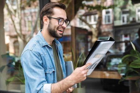 Photo of positive young man wearing eyeglasses reading newspaper while walking through city street with laptop in hand Zdjęcie Seryjne