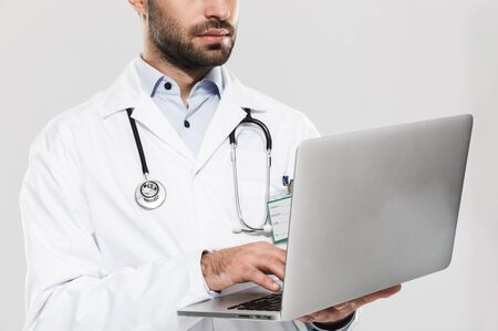Portrait of serious young medical doctor with stethoscope working in clinic and holding laptop isolated over white background Zdjęcie Seryjne
