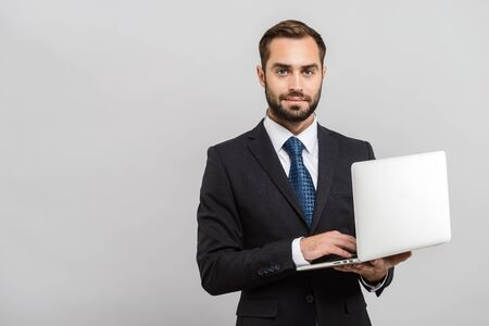 Attractive young businessman wearing suit standing isolated over gray background, using laptop computer