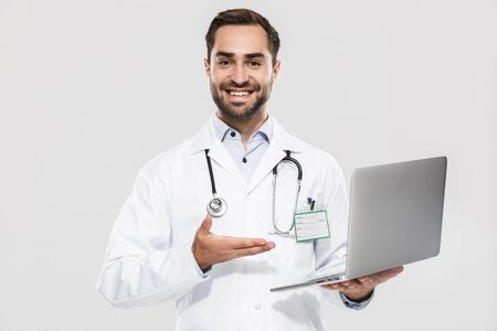 Portrait of cheerful young medical doctor with stethoscope working in clinic and holding laptop isolated over white background
