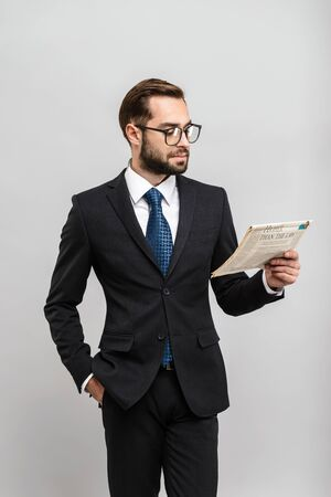 Handsome confident businessman wearing suit standing isolated over gray background, reading newspaper, wearing eyeglasses