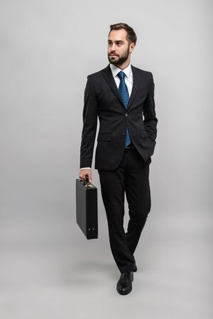 Full length of an attractive smiling young businessman wearing suit isolated over gray background, carrying briefcase, walking