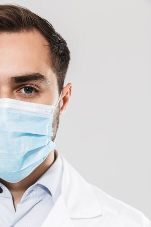 Portrait of brunette young medical doctor wearing sterile mask working in clinic laboratory and looking at camera isolated over white background Stock Photo - 128911281