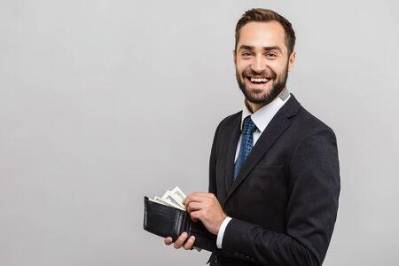 Aantrekkelijke gelukkige jonge zakenman die een pak draagt dat geïsoleerd staat over een grijze achtergrond, met een portemonnee vol geldbankbiljetten Stockfoto
