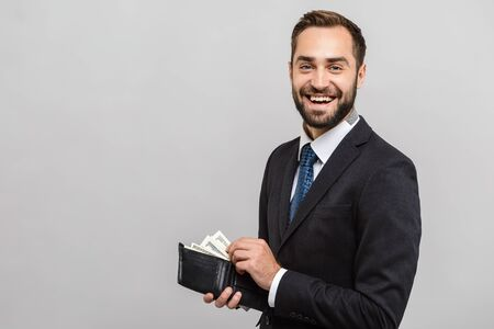Attractive happy young businessman wearing suit standing isolated over gray background, showing wallet full of money banknotes