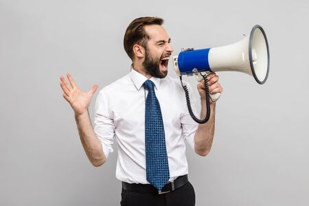 Portrait of a handsome young businessman wearing white shirt and tie standing isolated over gray background, holding loudspeaker, screaming