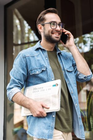 Foto eines intelligenten jungen Mannes mit Brille, der auf dem Smartphone spricht, während er mit Zeitung und Laptop in der Hand durch die Stadtstraße geht