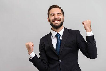 Jeune homme d'affaires séduisant portant un costume isolé sur fond gris, célébrant le succès Banque d'images