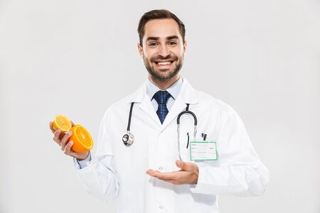 Attractive young cheerful male doctor wearing unifrom standing isolated over white background, showing sliced orange