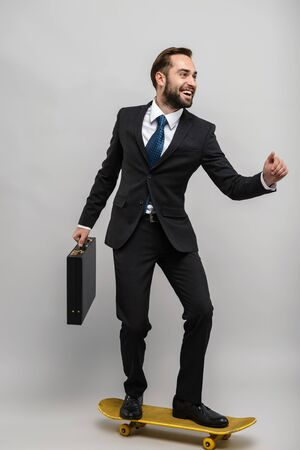 Full length of an attractive smiling young businessman wearing suit isolated over gray background, carrying briefcase while riding skateboard