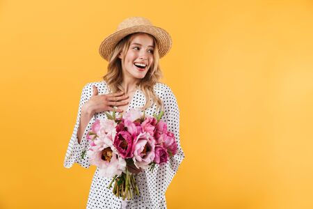 Portrait of a lovely young blonde girl wearing summer dress standing isolated over yellow background, holding peonies bouquet 스톡 콘텐츠