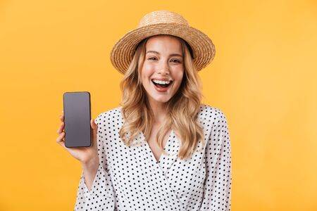Beautiful cheerful young blonde woman wearing summer dress standing isolated over yellow background, showing blank screen mobile phone 스톡 콘텐츠