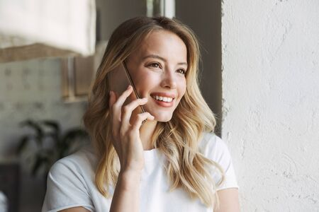 Close up of a beautiful young blonde woman at the cafe indoors, talking on mobile phone