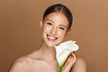Image of young woman smiling at camera and holding white flower isolated over beige background