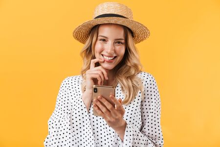 Portrait of a lovely cheerful young blonde girl wearing summer dress standing isolated over yellow background, using mobile phone