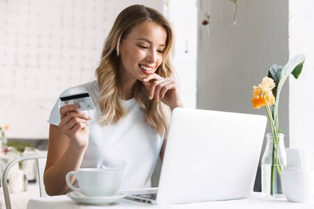 Image of a happy young pretty blonde woman sitting in cafe using laptop computer drinking coffee holding credit card.