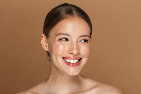 Image of happy woman smiling and looking aside isolated over beige background 스톡 콘텐츠