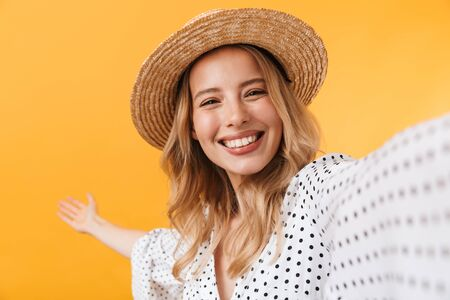 Portrait of a lovely young blonde girl wearing summer dress standing isolated over yellow background, taking a selfie 스톡 콘텐츠